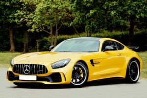 yellow color mercedes benz beside trees